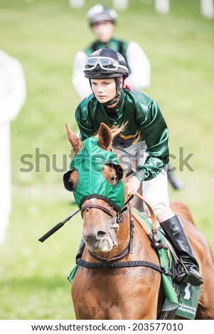 STOCKHOLM - JUNE 6: Woman jockey into a curve at the Nationaldags Galoppen in Gardet at a warm up lap. June 6, 2014 in Stockholm, Sweden. - stock photo