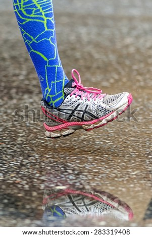 STOCKHOLM - MAY 30: Colored running shoe with blue socks reflecting in puddle at the wet streets of Stockholm in ASICS Stockholm Marathon 2015. - stock photo