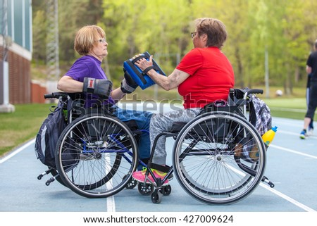 STOCKHOLM, MAY 2016, two disabled women in wheelchairs doing boxing as training exercise at the sport center Boson. - stock photo