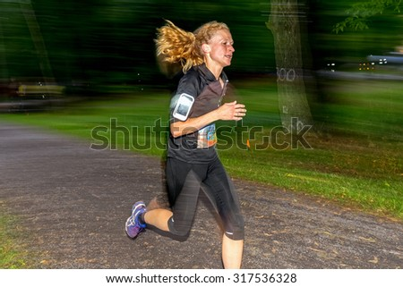 STOCKHOLM - SEP 16, 2015: Closeup of female runner with motion blur in forest at the event 5K EASD Run Walk to change diabetes at Stockholm Olympic Stadium with surroundings. - stock photo
