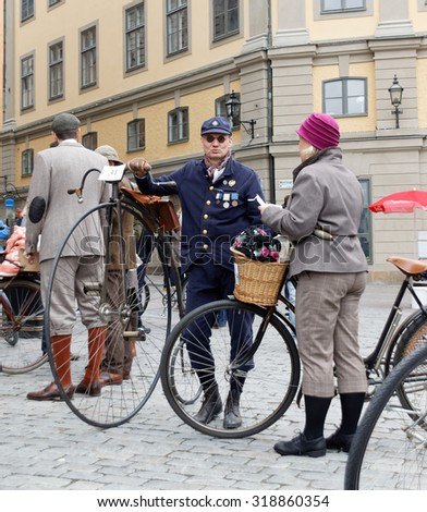 STOCKHOLM - SEPT 19, 2015: Man leading an very old bicycle and wearing old fashioned tweed clothes in the Bike in Tweed event September 19, 2015 in Stockholm, Sweden