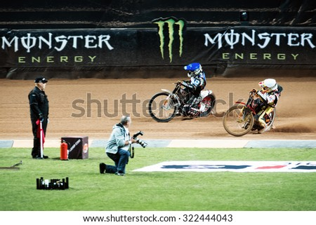 STOCKHOLM - SEPT 26, 2015: Speedway racers passing by photographer and official at the TEGERA Stockholm FIM Speedway Grand Prix at Friends Arena in Stockholm.