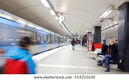Stockholm, Sweden - April 17, 2014: Upper platform at the metro station T-Centralen in Stockholm, Sweden, with people waiting and in motion when a subway train with destination Akeshov arrives.