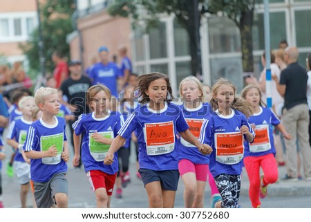 STOCKHOLM, SWEDEN - AUG 15, 2015: Two smiling girls holding hands and running in the running event Midnattsloppet, August 15, 2015 in Stockholm, Sweden - stock photo