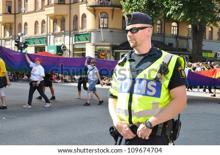 STOCKHOLM, SWEDEN - AUGUST 4: An unidentified policeman protects people taking part in Pride Parade 2012 to support gay rights on August 4, 2012 in Stockholm Sweden. - stock photo