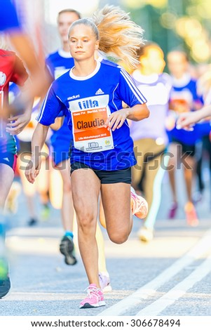 STOCKHOLM, SWEDEN - AUGUST 15, 2015: Blonde girl running just after the start at Lilla Midnattsloppet for aged 14. The track is 1775 meters and the runners are aged 8-15 years. - stock photo