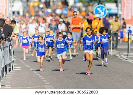 STOCKHOLM, SWEDEN - AUGUST 15, 2015: Fast group of kids at the Minimil for the youngest runners at Midnattsloppet. The track is 300 meters and the runners are aged 2-8 years. - stock photo