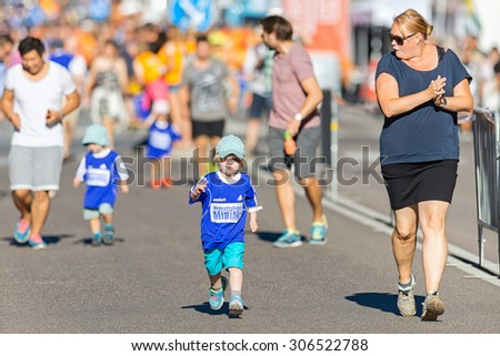 STOCKHOLM, SWEDEN - AUGUST 15, 2015: Kids with parents keeping them on track at the Minimil for the youngest runners at Midnattsloppet. The track is 300 meters and the runners are aged 2-8 years. - stock photo