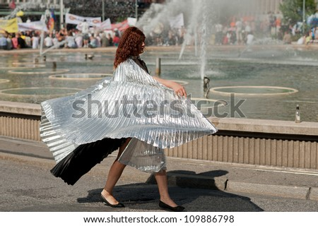 STOCKHOLM, SWEDEN - AUGUST 4: Woman in a fancy dress marching at Stockholm Pride Parade on August 4, 2012 in Stockholm which attracts an estimated 50000 participants and 500000 spectators. - stock photo