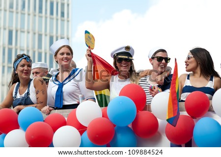 STOCKHOLM, SWEDEN - AUGUST 4: Women dressed as sailors at Stockholm Pride Parade on August 4, 2012 in Stockholm which attracts an estimated 50000 participants and 500000 spectators. - stock photo