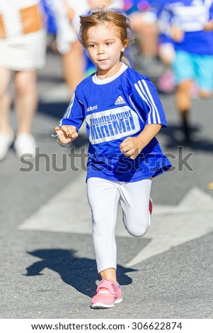 STOCKHOLM, SWEDEN - AUGUST 15, 2015: Young girl with a graceful style at the Minimil for the youngest runners at Midnattsloppet. The track is 300 meters and the runners are aged 2-8 years. - stock photo