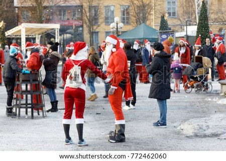 STOCKHOLM, SWEDEN - DEC 10, 2017: Many Santas in traditional red dresses on a square in the Stockholm Santa Run in Sweden, December 10, 2017