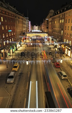Stockholm, Sweden - December 7, 2013: Night traffic on Kungsgatan in central Stockholm. Cars, pedestrians, taxis in traffic close to the crossing with Sveavagen