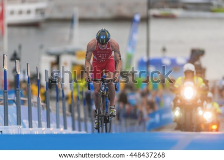 STOCKHOLM, SWEDEN - JULY 02, 2016: Lukas Pertl (AUT) cycling in backlight at the Mens ITU Triathlon event in Stockholm.