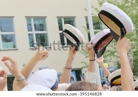 STOCKHOLM, SWEDEN - JUN 10, 2015: Graduation caps, hands and arms of celebrating graduation students after finishing high school at the school Globala gymnasiet, June 10, 2015, Stockholm, Sweden - stock photo