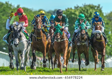 STOCKHOLM, SWEDEN - JUN 6, 2017: Group of horses with jockeys out of a curve in fast pace at Nationaldagsgaloppen at Gardet.