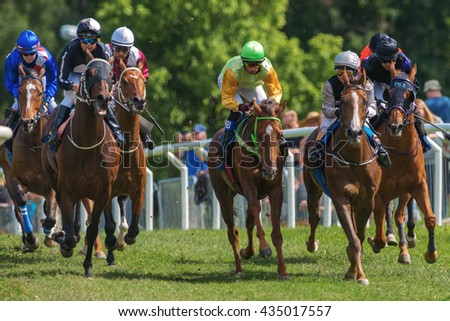 STOCKHOLM, SWEDEN - JUNE 6, 2016: Group of jockeys and race horses out of a curve at the Nationaldags Galoppen at Gardet with lush forest behind.