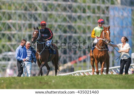 STOCKHOLM, SWEDEN - JUNE 6, 2016: Two  race horses stopped after the race by their trainers at the Nationaldags Galoppen at Gardet.