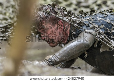 STOCKHOLM, SWEDEN - MAY 14, 2016 Crawling under the muddy net trap in Tough Viking obstacle course around Stockholm Stadion. - stock photo