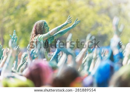 STOCKHOLM, SWEDEN - MAY 23: Girl sitting on friends shoulders with crowds arms waving around her at Stockholm Color Run in Tantolunden or Tanto on May 23, 2015. - stock photo