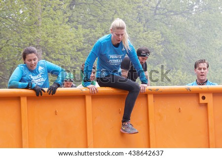 STOCKHOLM, SWEDEN - MAY 14, 2016: Group of woman and men climbing a orange container obstacle in the obstacle race Tough Viking Event in Sweden, May 14, 2016