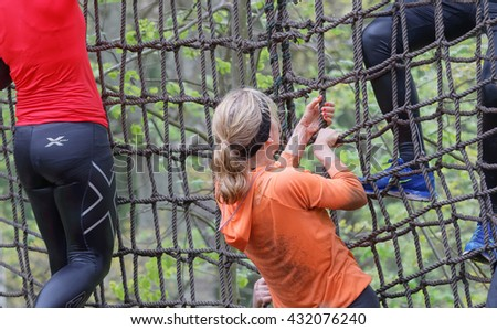 STOCKHOLM, SWEDEN - MAY 14, 2016: Group of woman climbing up a net in the obstacle race Tough Viking Event in Sweden, May 14, 2016
