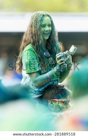 STOCKHOLM, SWEDEN - MAY 23: Happy girl covered in green color with camera in hands at Stockholm Color Run on May 23, 2015. People from all walks of life participated in the run. - stock photo