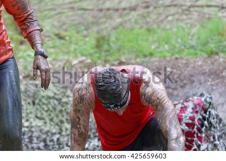 STOCKHOLM, SWEDEN - MAY 14, 2016: Man in red shirt covered with mud  bending forward in the forest in the obstacle race Tough Viking Event in Sweden, April 14, 2016