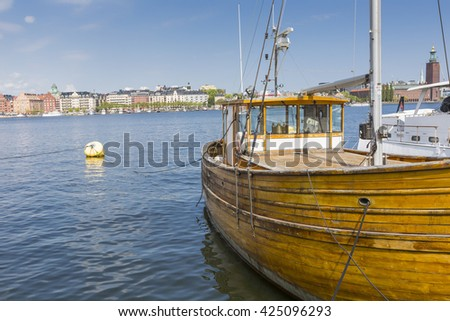 STOCKHOLM - SWEDEN -  21 MAY, 2016. Old city buildings and old boats on water under blue sky in Stockholm, Sweden.