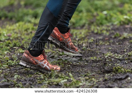 STOCKHOLM, SWEDEN - MAY 14, 2016 Tough Viking around Stockholm Stadion with the water and fire obstacle and closeup of muddy running shoes.