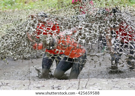 STOCKHOLM, SWEDEN - MAY 14, 2016: Woman and man covered with mud fighting to get out of a camouflage net in the obstacle race Tough Viking Event in Sweden, April 14, 2016