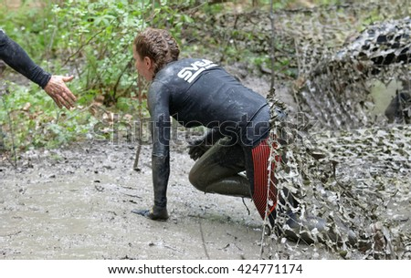 STOCKHOLM, SWEDEN - MAY 14, 2016: Woman covered with mud crawling under a camouflage net gets a helping hand  in the obstacle race Tough Viking Event in Sweden, April 14, 2016