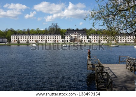 STOCKHOLM, SWEDEN - MAY 11: Young woman fishes on May 11, 2013 at Kungsholms Strand in Stockholm. Karlberg palace in the background is the home of the Swedish military academy. - stock photo