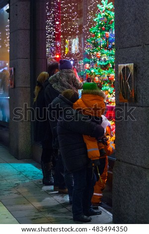 STOCKHOLM, SWEDEN - NOV 26: Christmas atmosphere of the city at night. Parents & children view a holiday showcase. Christmas Fair. NK Stockholm. Hamngatan. Stockholm. Sweden. Europe. November 26, 2010