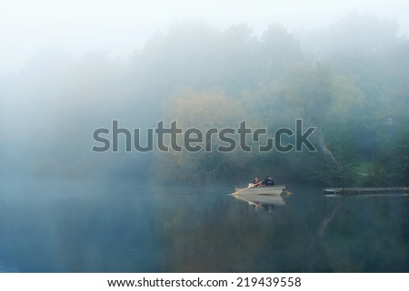 Stockholm, Sweden - Sep 19, 2014: Two men inspecting lake Trekanten with a rowing boat during a early misty morning in Stockholm, Sweden - stock photo