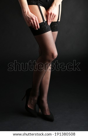 Stockings on perfect woman legs on dark background - stock photo