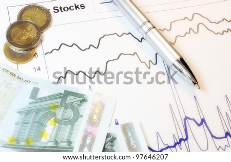 Stocks graph with coins, paper money and a pen as a concept of stock market.
