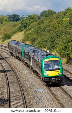STOKE POUND, UK - AUGUST 4: A local London Midland commuter service heads toward the suburbs of Birmingham on August 4, 2014 in Stoke Pound. London Midland call at 146 stations operating over 868Km - stock photo