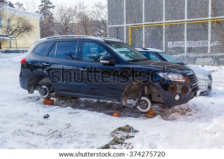stolen car without wheels winter morning on the Russian car park - stock photo