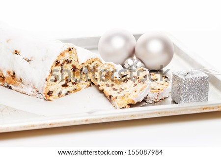 stollen cake for christmas on a silver metal tray with a silver christmas balls and small christmas present - stock photo