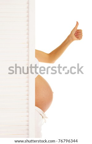 stomach and hand pregnant woman looked out from behind the door isolated on white - stock photo