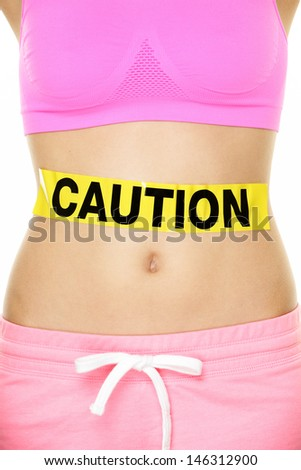 Stomach health warning concept showing woman belly CAUTION sign. Take care of your body, food poisoning or other digestion concept. Conceptual healthy lifestyle image. - stock photo
