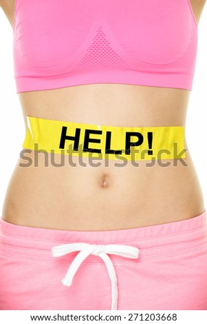 Stomach help concept - woman with body weight problem. Closeup of waist of female adult showing yellow label on abdomen with word HELP written for digestion, health, reproduction or diet issues. - stock photo