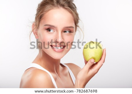 Stomatology concept, girl with strong white teeth looking aside and smiling, holding green apple in hand. Closeup of young woman at dentist's, studio, indoors