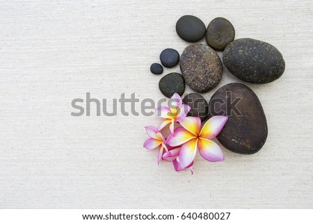 Stone and fresh flower on canvas texture background, spa decorate background