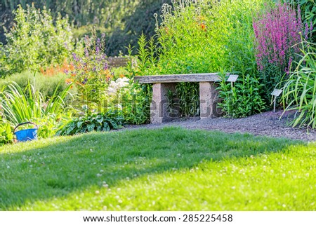 Stone and wood bench in garden - stock photo