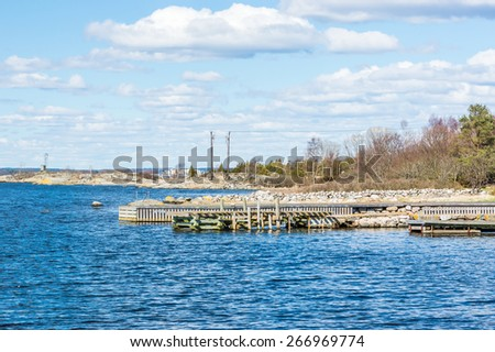 Stone and wooden bridges in the archipelago. Coastline of island, blue water and cloudy sky. Early spring. No boats or people. - stock photo