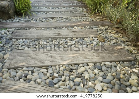 stone and wooden plank paving on walkway in garden - stock photo