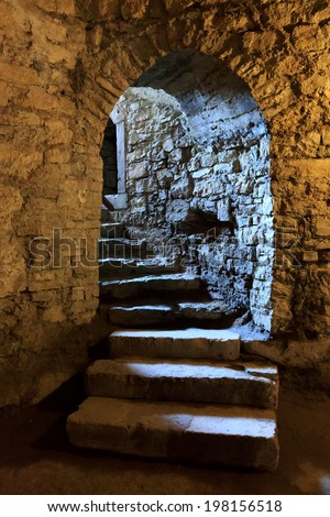 Stone arch and steps in underground castte - stock photo