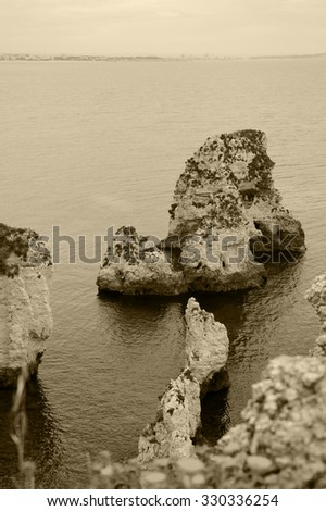 Stone arches, caves, rock formations at Dona Ana Beach (Lagos, Algarve coast, Portugal) in evening light. Blurred flowers at foreground. Silhouettes of city buildings on horizon. Aged photo. Sepia. - stock photo
